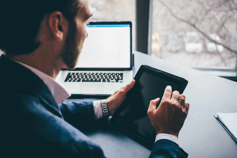 businessman-working-on-digital-tablet-close-up-han-ZPSB6RN