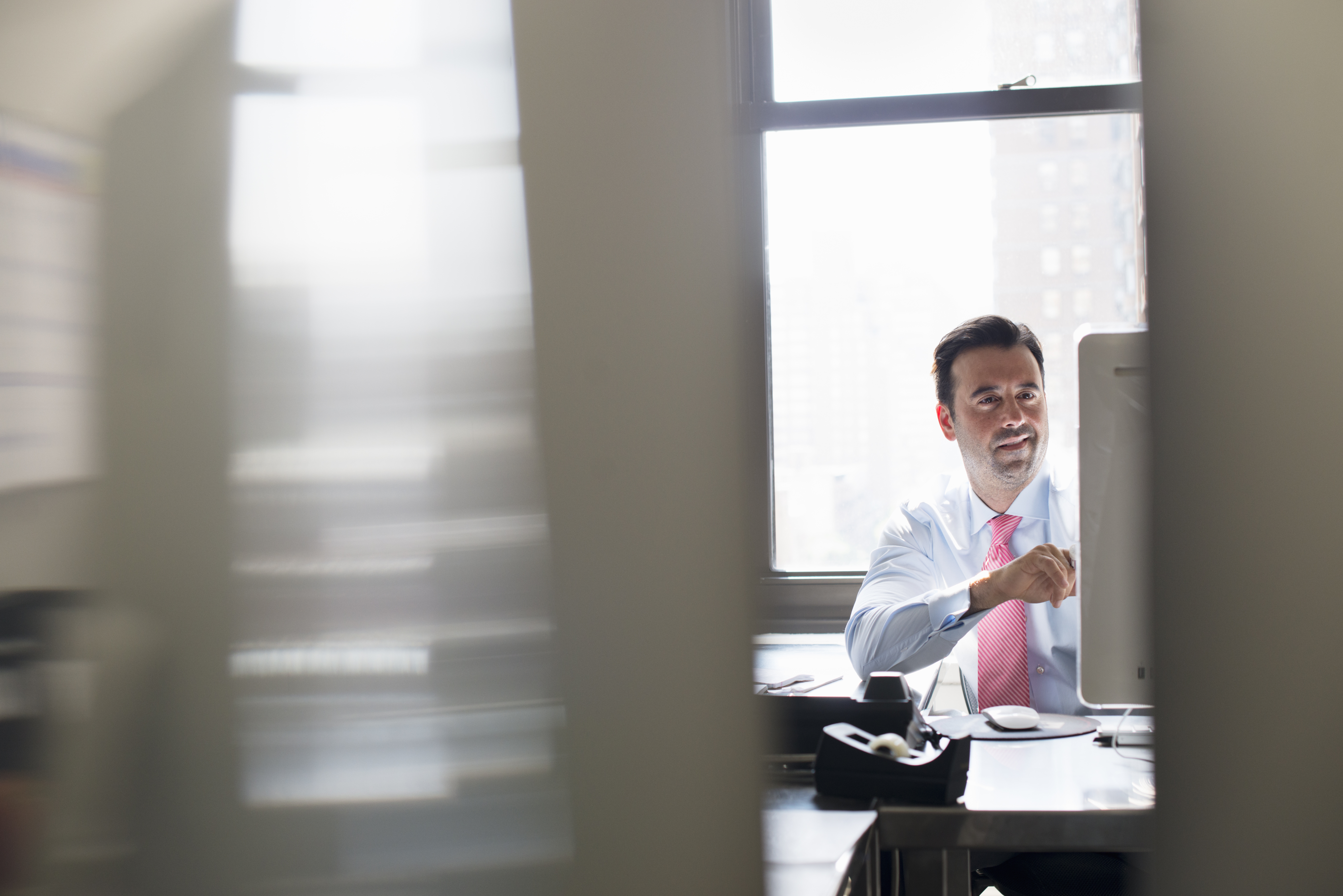 security-risk-a-man-in-shirt-and-tie-seated-at-a-desk-looking-at